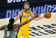 Indiana Pacers forward Domantas Sabonis (11) looks to pass the ball around Brooklyn Nets center DeAndre Jordan (6) during the first half of an NBA basketball game in Indianapolis, Wednesday, March 17, 2021. (AP Photo/Michael Conroy)