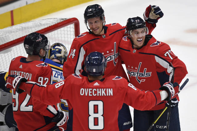 Washington Capitals right wing Richard Panik (14) is surrounded by his teammates after scoring the game-winning goal during the third period of an NHL preseason hockey game in Washington, Wednesday, Sept. 18, 2019. The Capitals beat the Blues, 3-2. Panik is joined by teammates Evgeny Kuznetsov (92), Alex Ovechkin (8), and T.J. Oshie (77). (AP Photo/Susan Walsh)