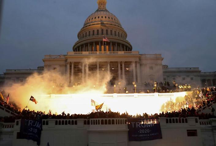 An explosion caused by a police munition is seen while Trump supporters gather in front of the Capitol.