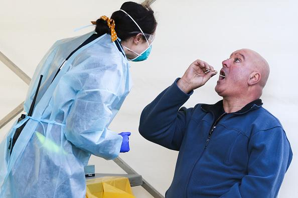 A man conducts a supervised swab test at a COVID-19 pop up testing centre in the hotspot suburb of Brunswick West in Melbourne, Australia.
