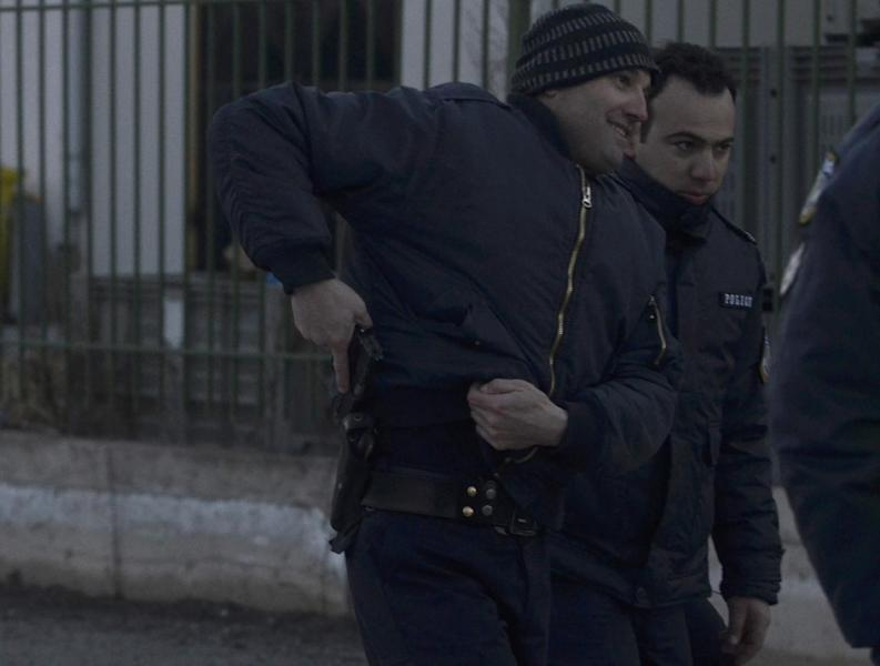 A police officer holsters his gun after checking it as he secures with colleagues the area around a factory in the northern city of Komotini, about 800 kilometers (500 miles) northeast of Athens, Thursday, March 1, 2012. An unemployed man shot and wounded two people and took two others hostage at the plastics factory. The shooter, who was fired from the factory eight months ago, burst into the site with a with a shotgun, wounding a member of the management and another employee, police said. (AP Photo/Nikolas Giakoumidis)