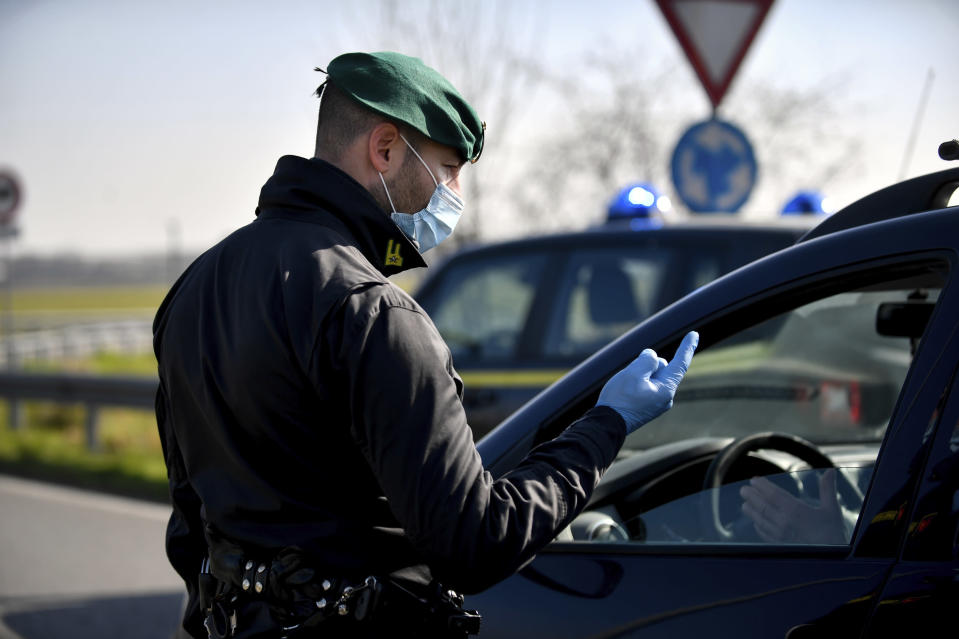 A tax police officer wearing a sanitary mask talks to a driver at a road block in Casalpusterlengo, Northern Italy, Monday, Feb. 24, 2020. Italy scrambled to check the spread of Europe's first major outbreak of the new viral disease amid rapidly rising numbers of infections. Road blocks were set up in at least some of 10 towns in Lombardy at the epicenter of the outbreak, to keep people from leaving or arriving. (Claudio Furlan/Lapresse via AP)