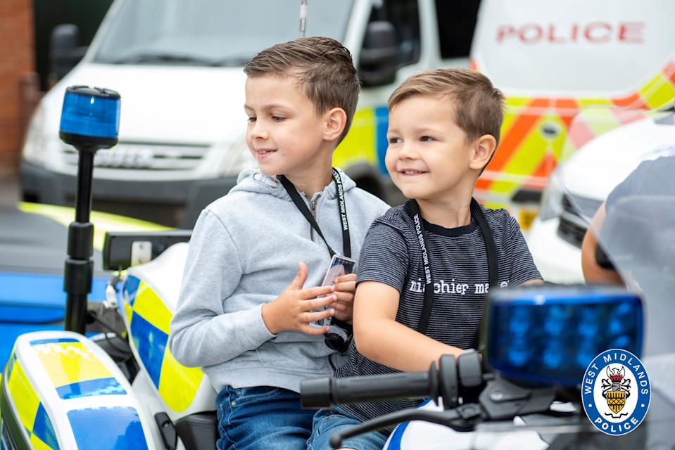 """Young and blind Oscar Jealous aged 8 (left) on his 'dream day' getting a special tour of West Midlands Police's Bournville station with his brother Charlie. See SWNS story SWMDwish. A young boy who lost his sight due to a rare life-limiting disease enjoyed a """"dream day"""" by becoming an honorary police officer, ticking off one of the items on his bucket list. Oscar Jealous, 8, from Kingstanding, Birmingham, recently spent the day with West Midlands Police at Bournville station. The youngster, who suffers from the degenerative Batten disease, went behind the wheel of a police car, played custody sergeant in the cell blocks and cuddled the new puppy recruits. He and his younger brother Charlie were also given warrant cards as a memento."""