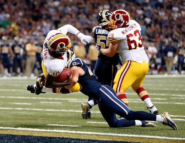 ST LOUIS, MO - SEPTEMBER 16: Quarterback Robert Griffin III #10 of the Washington Redskins lunges over the goal line for a touchdown as strong safety Craig Dahl #43 of the St. Louis Rams defends during the game against the St. Louis Rams at Edward Jones Dome on September 16, 2012 in St Louis, Missouri. (Photo by Jamie Squire/Getty Images)