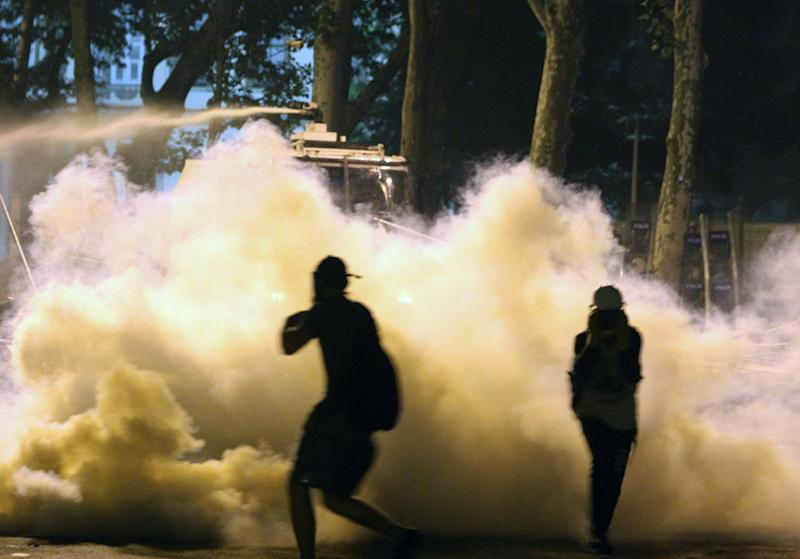 Police use water cannon as protesters run to avoid tear gas during the third day of nationwide anti-government protest near the Prime Minister's office at Besiktas area in Istanbul, late Sunday, June 2, 2013.  Protests in Istanbul and several other Turkish cities appear to have subsided, after days of fierce clashes following a police crackdown on a peaceful gathering. The demonstrations grew out of anger over a violent police crackdown of a peaceful environmental protest at Istanbul's Taksim Square and spread to other Turkish cities. (AP Photo/Thanassis Stavrakis)