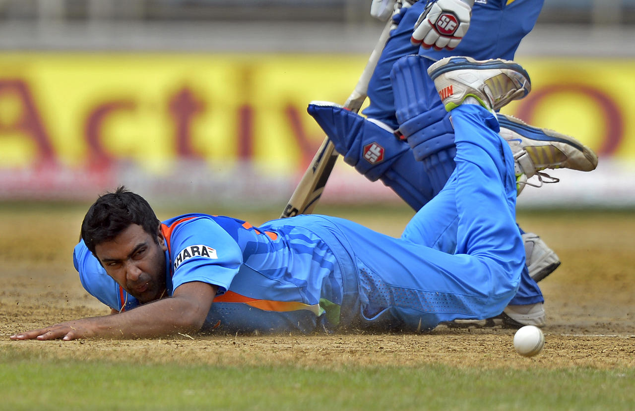Indian cricketer Ravichandran Ashwin dives on the gournd to field a ball during the third match of the Tri-Nation series between India and Sri Lanka at the Sabina Park stadium in Kingston on July 2, 2013. Indian won the toss and elected to filed first. AFP PHOTO/Jewel Samad