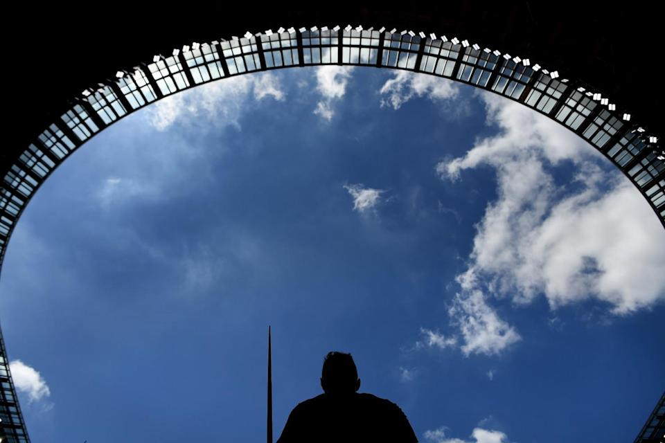 An athlete stands in the shade before the start of the men's javelin throw.
