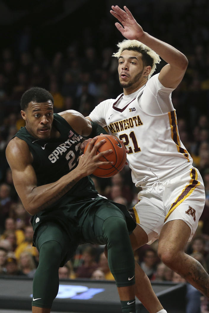 Michigan State's Xavier Tillman, left, handles the ball against Minnesota's Jarvis Omersa during an NCAA college basketball game Sunday, Jan. 26, 2020, in Minneapolis. (AP Photo/Stacy Bengs)