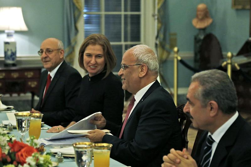 Israel's Justice Minister and chief negotiator Tzipi Livni, second left, Palestinian chief negotiator Saeb Erekat, second right, Yitzhak Molcho, an adviser to Israeli Prime Minister Benjamin Netanyahu, left, and Mohammed Shtayyeh, aide to Palestinian President Mahmoud Abbas, right, are seated across from Secretary of State John Kerry, not pictured, at an Iftar dinner, which celebrates Ramadan, at the State Department in Washington, marking the resumption of Israeli-Palestinian peace talks, Monday, July 29, 2013. (AP Photo/Charles Dharapak)