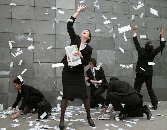 People in suits gathering money falling from the sky.