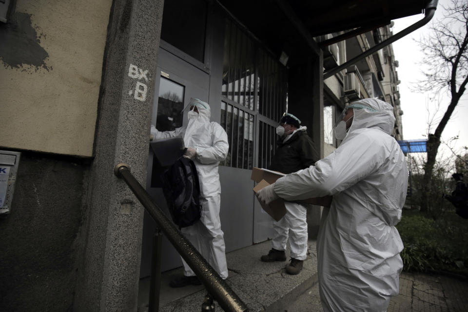 People dressed in protective clothing representing COVID-19 mobile polling station go to address of sick people for their casting vote, Sofia, Bulgaria, Sunday, April 4, 2021. Bulgarians are heading to the polls on Sunday to cast ballots for a new parliament after months of anti-government protests and amid a surge of coronavirus infections. (AP Photo/Valentina Petrova)