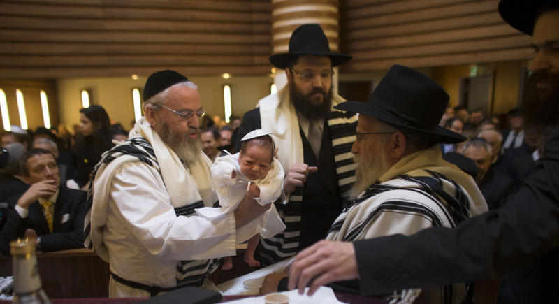 FILE - In this Sunday, March 3, 2013 file photo Mohel Manachem Fleischmann, left, holds baby Mendl Teichtal after the circumcision ceremony at the Chabad Lubawitsch Orthodox Jewish synagogue in Berlin, Germany. A new survey says about one in four Europeans hold anti-Semitic beliefs, with such attitudes on the rise in eastern countries and mostly steady in the west. (AP Photo/Markus Schreiber, file)