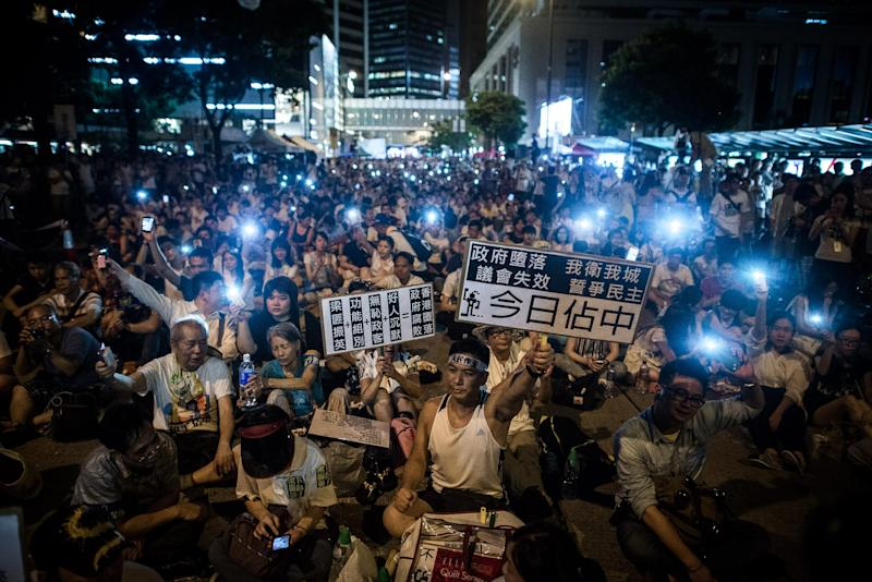 Demonstrators sit in a street of the central district after a pro-democracy rally seeking greater democracy in Hong Kong on July 1, 2014 (AFP Photo/Philippe Lopez)