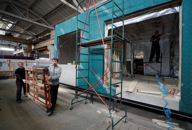 Employees of Unitfab work on the construction of a prefab house in Kiev