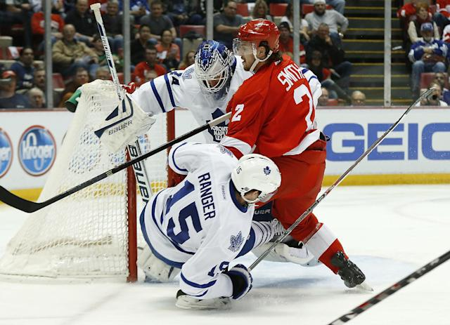 Detroit Red Wings forward Brendan Smith (2) and Toronto Maple Leafs defenseman Paul Ranger (15) collide with Toronto Maple Leafs goalie James Reimer in the second period of an NHL hockey game in Detroit, Tuesday, March 18, 2014. (AP Photo/Paul Sancya)