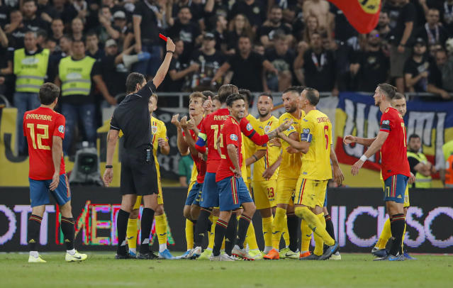 Spain's Diego Llorente, center receives a red card during the Euro 2020 group F qualifying soccer match between Romania and Spain, at the National Arena stadium in Bucharest, Romania, Thursday, Sept. 5, 2019. (AP Photo/Vadim Ghirda)