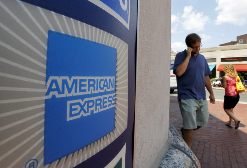 FILE - In this July 19, 2011, file photo, passers-by walk past an American Express logo near the entrance to a bank in the Harvard Square neighborhood of Cambridge, Mass. American Express posted a 6 percent increase in profits for the first quarter, Thursday, April 16, 2015, but the company's results took a hit from a stronger U.S. dollar. (AP Photo/Steven Senne, File)