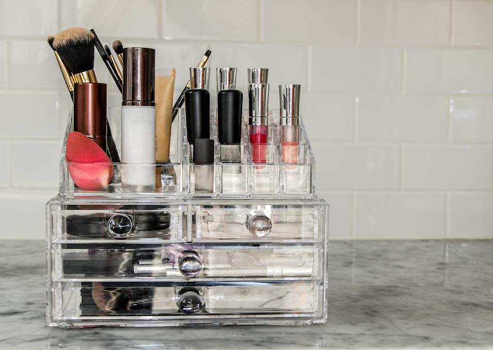 Transparent makeup organizer with numerous items.