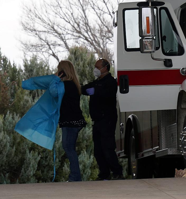 EMT Ericka Nicholson dons a protective gown in preparation for transporting a COVID-19 positive patient from Quinter, Kansas, to a larger hospital for treatment, assisted by fellow EMT Roy Litfin.