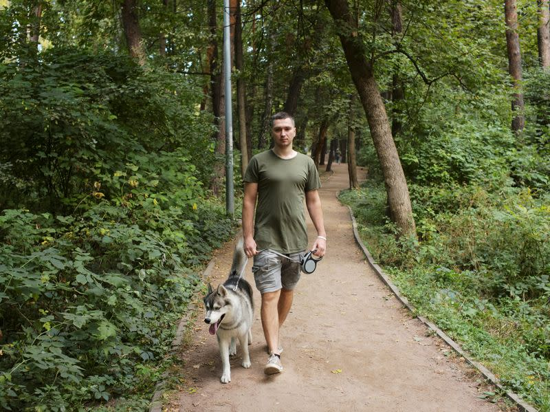 Belarusian software engineer Max Korolevsky walks with his dog in Kyiv