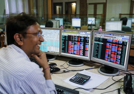 A broker laughs while speaking to a colleague, as they trade on their computer terminals at a stock brokerage firm in Mumbai