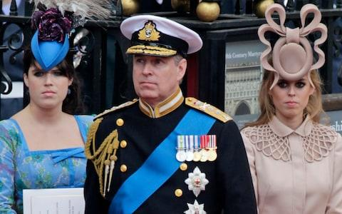 Prince Andrew, center, and his daughters Princess Eugenie, left, and Princess Beatrice at the wedding of Prince William to Catherine Middleton - Credit: Gero Breloer/AP