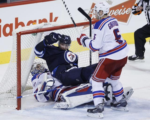 Winnipeg Jets' Blake Wheeler (26) gets checked into New York Rangers goaltender Henrik Lundqvist (30) by Dan Girardi (5) during third period NHL action in Winnipeg on Friday, March 14, 2014. (AP Photo/The Canadian Press, John Woods)
