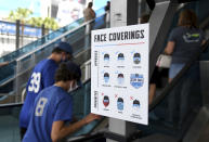 A health and safety sign is displayed on the ground level of loanDepot park prior to the opening day baseball game between the Tampa Bay Rays and the Miami Marlins, Thursday, April 1, 2021, in Miami. (AP Photo/Gaston De Cardenas)