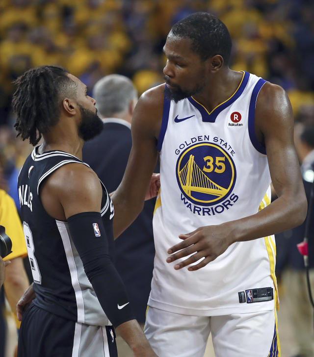 Golden State Warriors' Kevin Durant, right, speaks with San Antonio Spurs' Patty Mills at the end of Game 5 of a first-round NBA basketball playoff series Tuesday, April 24, 2018, in Oakland, Calif. The Warriors won 99-91, eliminating the Spurs from the playoffs. (AP Photo/Ben Margot)