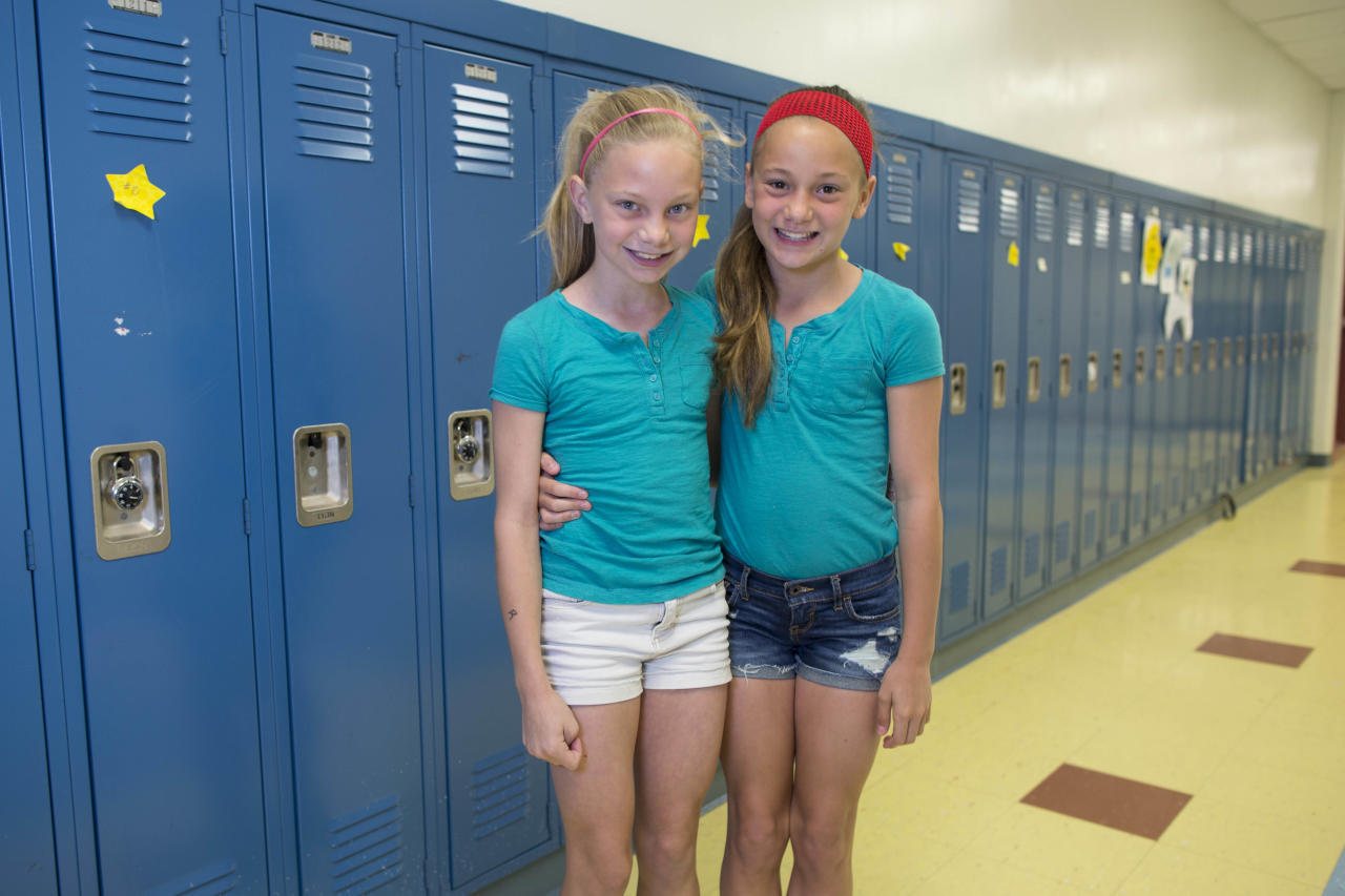 In this Thursday, June 6, 2013 photo, Gracie Ramsey, left, and her twin sister, Julia, one of the twenty-four sets of twins from Highcrest Middle School in Wilmette, Ill., pose for a portrait at the school. The group is attempting to break a Guinness World record for the amount of twins in one grade which is currently sixteen sets. (AP Photo/Scott Eisen)