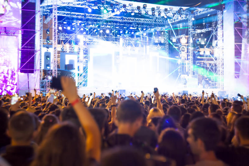 Crowd of people in front of a brightly lit concert stage.
