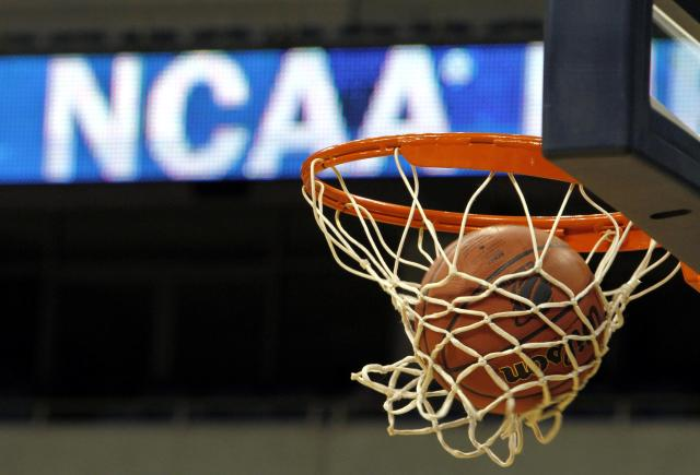FILE - In this March 20, 2010, file photo, a ball flicks through the net in front of the NCAA logo on the marquis during an NCAA college basketball practice in Pittsburgh. Defying the NCAA, California's governor signed a first-in-the-nation law Monday, Sept. 30, that will let college athletes hire agents and make money from endorsements a move that could upend amateur sports in the U.S. and trigger a legal challenge. (AP Photo/Keith Srakocic, File)
