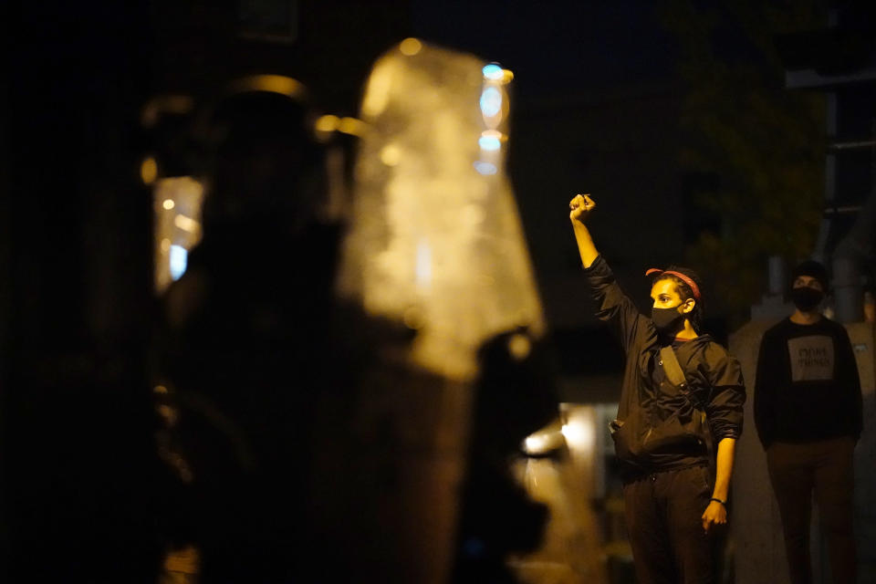 A demonstrator raises a fist near Philadelphia police in Philadelphia, late Tuesday, Oct. 27, 2020. Hundreds of demonstrators marched in West Philadelphia over the death of Walter Wallace Jr., a Black man who was killed by police in Philadelphia on Monday. Police shot and killed the 27-year-old on a Philadelphia street after yelling at him to drop his knife. (AP Photo/Matt Slocum)