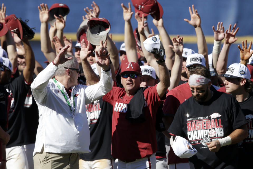 Arkansas coach Dave Van Horn, center, celebrates with the team after defeating Tennessee in an NCAA college baseball championship game during the Southeastern Conference tournament Sunday, May 30, 2021, in Hoover, Ala. (AP Photo/Butch Dill)