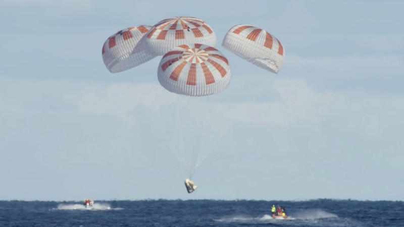 In this Friday, March 8, 2019 image from video made available by SpaceX, the company's Crew Dragon descends to the Atlantic Ocean for a splashdown after a deorbit burn to reenter Earth's atmosphere, returning from the International Space Station. (SpaceX via AP)