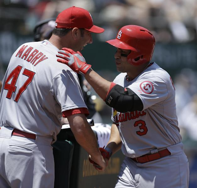 St. Louis Cardinals' Carlos Beltran, right, is congratulated by hitting coach John Mabry (47) after Beltran hit a two run home run off Oakland Athletics' Tommy Milone in the first inning of a baseball game Sunday, June 30, 2013, in Oakland, Calif. (AP Photo/Ben Margot)