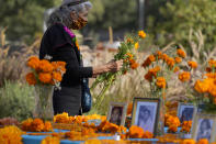 "Artist and altar maker Ofelia Esparza, 88, from East Los Angeles, brings fresh marigolds for her community altar for Day of the Dead, titled ""2020 Memorial to Our Resilience,"" at Grand Park in Los Angeles, Thursday, Oct. 29, 2020. Day of the Dead, or Dia de los Muertos, the annual Mexican tradition of reminiscing about departed loved ones with colorful altars, or ofrendas, is typically celebrated Sunday through Monday. It will undoubtedly be harder for Latino families in the U.S. torn apart by the coronavirus. (AP Photo/Damian Dovarganes)"