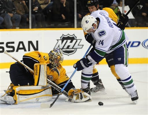 Nashville Predators goalie Pekka Rinne, left, of Finland, stops a shot by Vancouver Canucks right wing Alex Burrows (14) during the first period of an NHL hockey game on Tuesday, Feb. 7, 2012, in Nashville, Tenn. (AP Photo/Mike Strasinger)