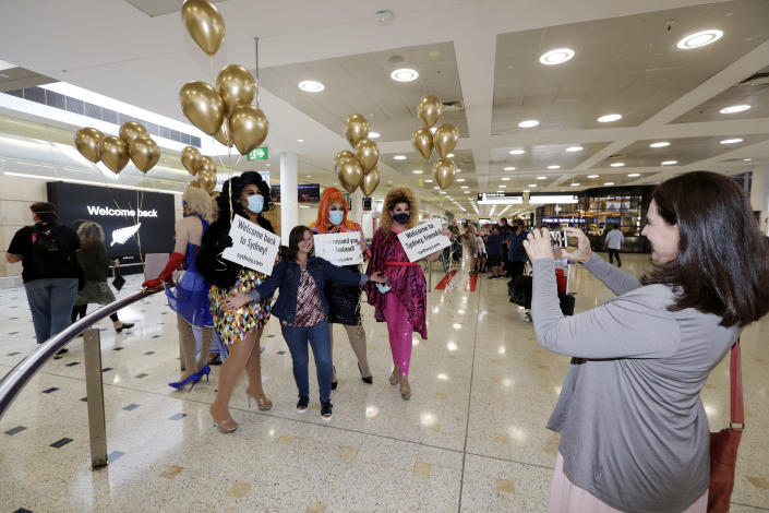 A passenger from New Zealand, center, poses with drag queens as they welcome her at Sydney Airport in Sydney, Australia, Monday, April 19, 2021, as the much-anticipated travel bubble between Australia and New Zealand opens. (AP Photo/Rick Rycroft)