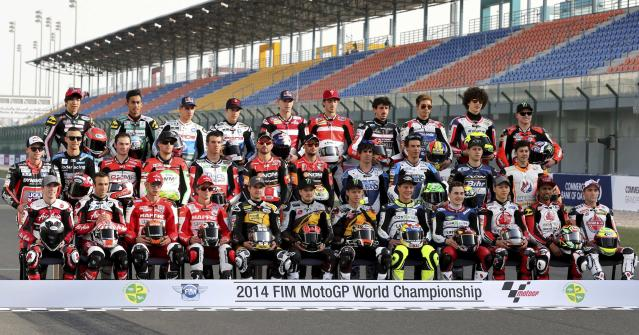 Moto2 riders pose for a group photo before the start of the free practice session of the MotoGP World Championship at the Losail International circuit in Doha March 20, 2014. REUTERS/Fadi Al-Assaad (QATAR - Tags: SPORT MOTORSPORT)
