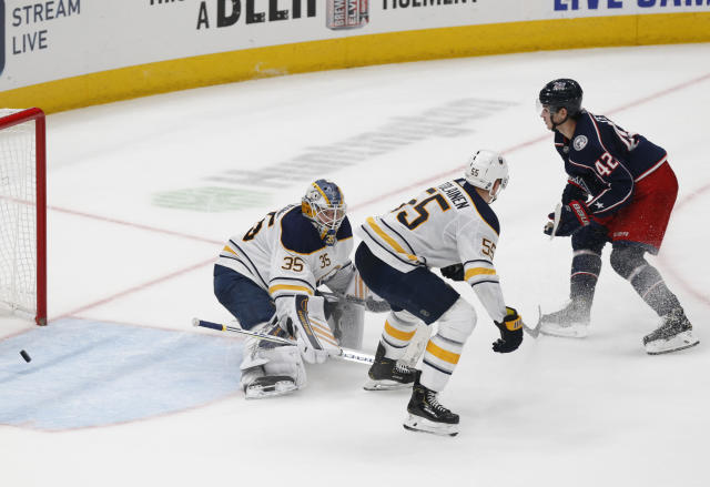 Columbus Blue Jackets forward Alexandre Texier, right, of France, watches his winning goal past Buffalo Sabres goalie Linus Ullmark, left, of Sweden, and defenseman Rasmus Ristolainen, of Finland, during an overtime period of an NHL hockey game in Columbus, Ohio, Monday, Oct. 7, 2019. (AP Photo/Paul Vernon)