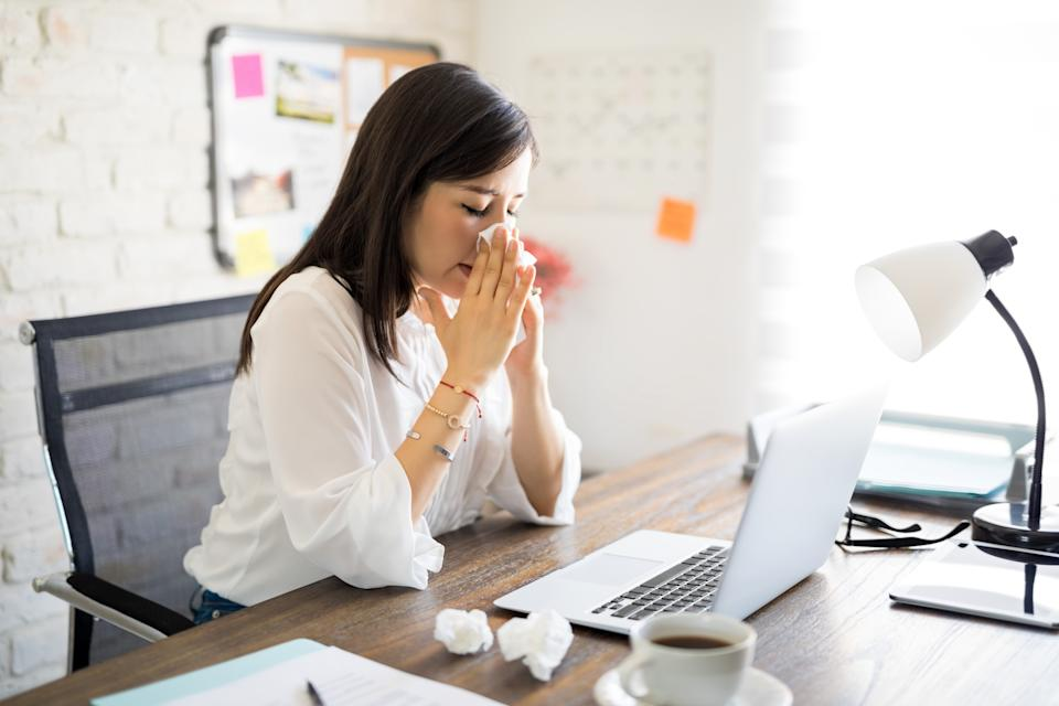 Young sick woman sitting in the office desk with laptop and wiping nose with paper napkin