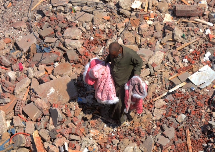 A man walks on the rubble of a collapsed apartment building in the el-Salam neighborhood, in Cairo, Egypt, Saturday, March 27, 2021. A nine-story apartment building collapsed in the Egyptian capital early Saturday, killing at several and injuring about two dozen others, an official said. (AP Photo/Tarek wajeh)