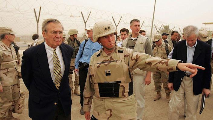 Secretary of Defense Donald Rumsfeld (L) is briefed about detainee operations by Major General Geoffry Miller (2nd L), the Deputy Director of Detainee Operations for Iraq while touring the Abu Ghraib Prison Facility May 13, 2004 outside Baghdad, Iraq