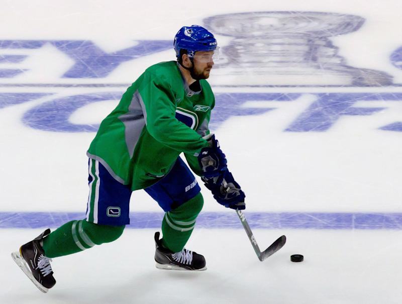 Vancouver Canucks' Keith Ballard skates past a logo of the Stanley Cup painted under the ice during practice in Vancouver, British Columbia, on Monday May 23, 2011. The Canucks and the San Jose Sharks are scheduled to play Game 5 of the NHL hockey Stanley Cup playoff Western Conference finals on Tuesday. (AP Photo/The Canadian Press, Darryl Dyck)