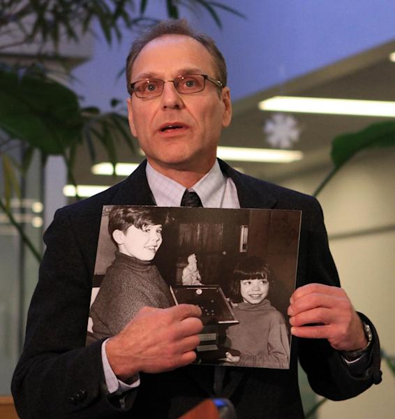 Assistant Alaska Attorney General Neil Slotnick displays a decades-old photo of moon rocks presented to the state of Alaska on Thursday, Dec. 6, 2012, at a press conference at Anchorage School District offices in Anchorage, Alaska. Slotnick says the photo helped establish the authenticity of a moon rock display presented by President Richard Nixon to Alaska in 1969. The rocks disappeared after a museum fire in 1973 but were returned to Alaska Wednesday. (AP Photo/Dan Joling)