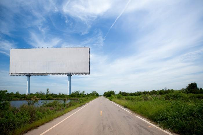 Blank billboard next to a clear country highway.