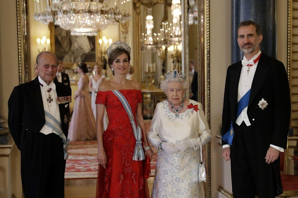 """<p>Queen Letizia and King Felipe VI of Spain pose for a photo with <a href=""""https://www.townandcountrymag.com/society/g9234793/queen-elizabeth-facts/"""" rel=""""nofollow noopener"""" target=""""_blank"""" data-ylk=""""slk:Queen Elizabeth II"""" class=""""link rapid-noclick-resp"""">Queen Elizabeth II</a> and <a href=""""https://www.townandcountrymag.com/society/politics/a9190075/who-is-prince-philip/"""" rel=""""nofollow noopener"""" target=""""_blank"""" data-ylk=""""slk:Prince Philip"""" class=""""link rapid-noclick-resp"""">Prince Philip</a> before a State Banquet at Buckingham Palace.</p>"""