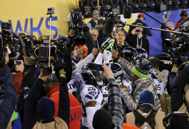 Seattle Seahawks players huddle after their warm up as cameras surround them before the NFL Super Bowl XLVIII football game against the Denver Broncos Sunday, Feb. 2, 2014, in East Rutherford, N.J. (AP Photo/Matt York)