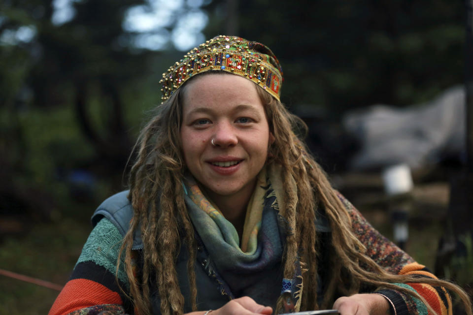 Rainbow Gathering participant Kendra Strebig poses for a photo on Friday, July 2, 2021, in the Carson National Forest, outside of Taos, N.M. More than 2,000 people have made the trek into the mountains of northern New Mexico as part of an annual counterculture gathering of the so-called Rainbow Family. While past congregations on national forest lands elsewhere have drawn as many as 20,000 people, this year's festival appears to be more reserved. Members (AP Photo/Cedar Attanasio)